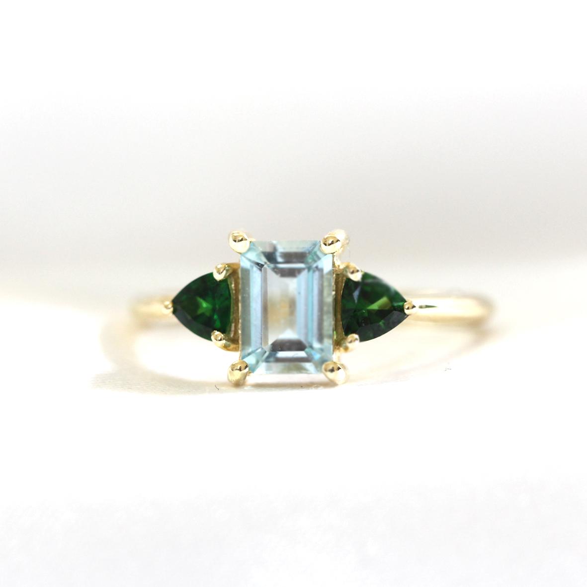 טבעת זהב משובצת אקוואה מרין בחיתוך אמרלד קאט וטורמלין ירוק בחיתוך טריליון בצדדים
